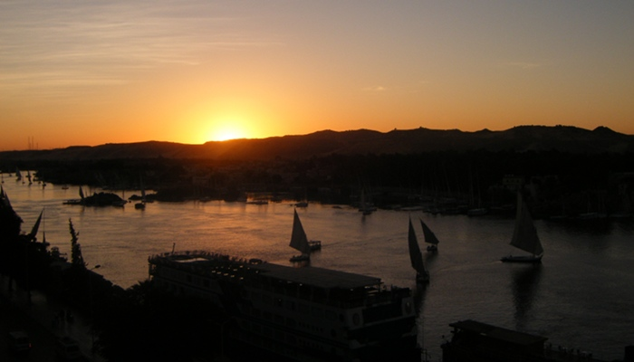 Feluccas and cruise ships on the Nile in Aswan at sunset.