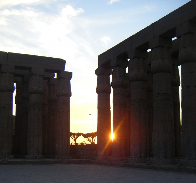 The sun setting through columns at Luxor Temple.