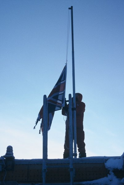 The oldest winterer lowering the British flag on the last day the sun was above the horizon during the winter.